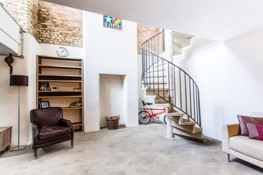 The modern 'Upstairs Downstairs'. Dingley Place's unusual layout places the bedroom space below the living room area, connected by a spiral staircase.