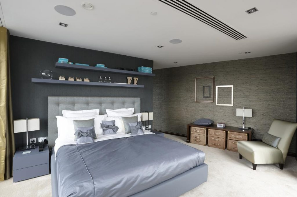 Old Street Penthouse boasts stylish fabrics and textures; the fabric effect on the walls in this bedroom and carpeted floors give this room a relaxing, soft finish